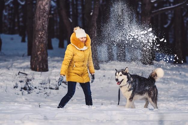 Красивая молодая девушка смешно играет со своей собакой зимой в парке