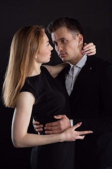 A beautiful young girl gently embraces a man who looks into her eyes tenderly