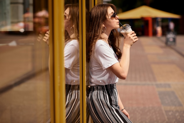 Beautiful young girl  in glasses drinks a cold latte on a hot summer day