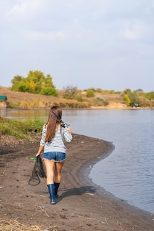 A beautiful young girl goes fishing. a girl with a fishing rod and a cage in hand is walking along the lake
