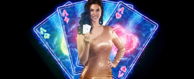 A beautiful young girl in a gold dress holds playing cards, neon casino inscription, cards and dice in her hands. banner concept for casino, poker, flyer, gambling, croupier, header for the site.