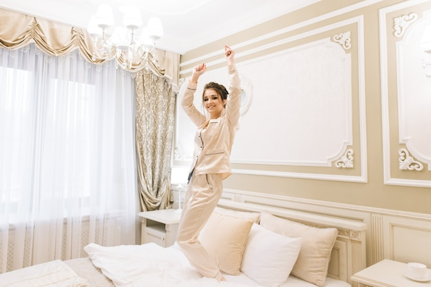 Beautiful young girl in golden pajamas in a luxurious room