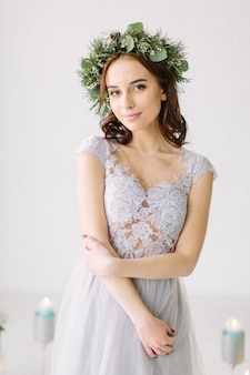 Beautiful young girl in a gray evening dress and a wreath of pine and eucalyptus on her head poses