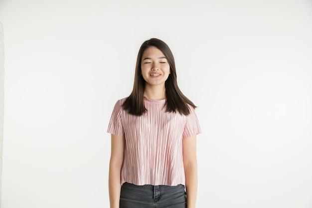 Портрет красивой молодой девушки поясной, изолированные на белой стене студии
