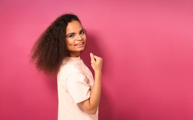 Красивая молодая девушка наполовину повернулась и положительно смотрит вперед в персиковой футболке, показывая свои мускулы, изолированные на розовой стене