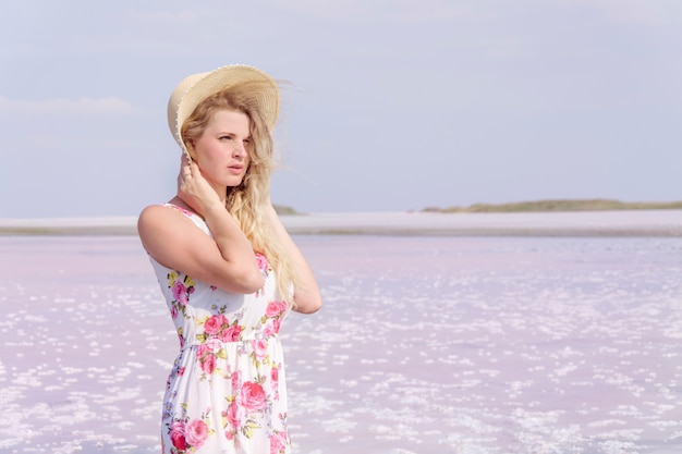 Beautiful young girl in a hat on a background of pink lake.
