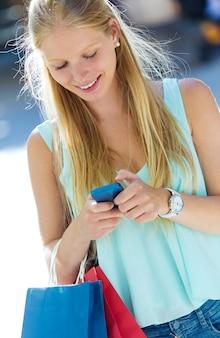スマートフォンで楽しむ美しい若い女の子。