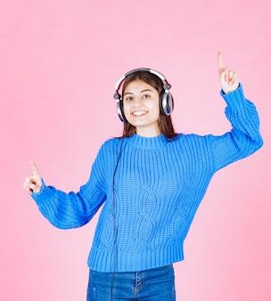 Bella ragazza in cuffie che ascolta musica e balla sul rosa.