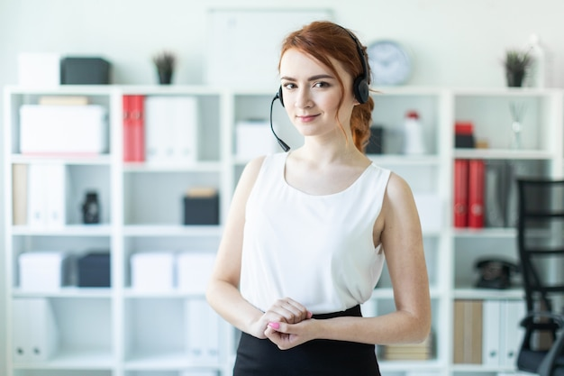 Beautiful young girl in headphones with microphone standing in office.