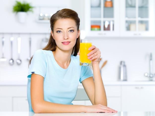 美しい少女は新鮮なオレンジジュースのグラスを保持します。