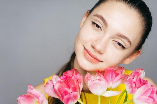 향기로운 분홍색 꽃의 큰 꽃다발을 들고 웃고 있는 아름다운 소녀