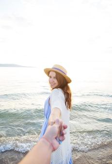 Красивая молодая девушка держит парня за руку и смотрит на море