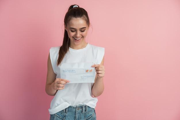 Красивая, молодая девушка держит конверт