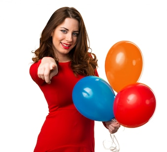Beautiful young girl holding balloons and pointing to the front