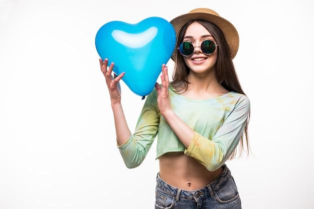 Bella ragazza che tiene un aerostato di aria del cuore blu. il concetto di san valentino