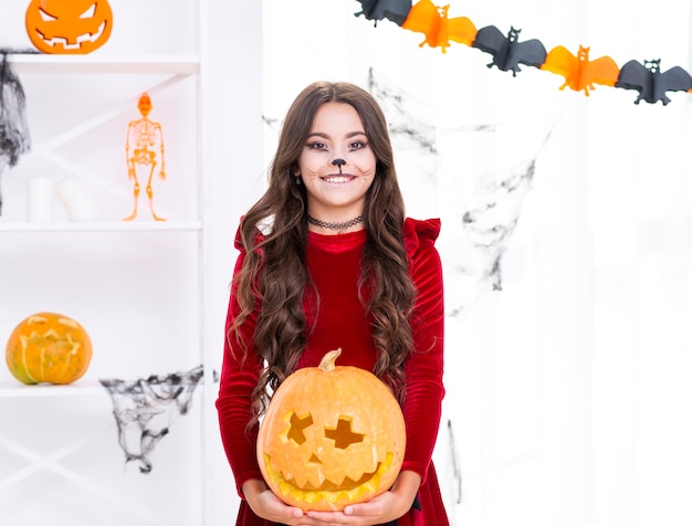 Beautiful young girl holding carved pumpkin