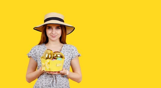 Красивая молодая девушка держит красочные яйца, глядя на копию пространства