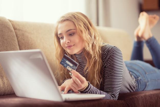 Красивая молодая девушка, держащая кредитную карту, покупая онлайн на софе в гостиной.