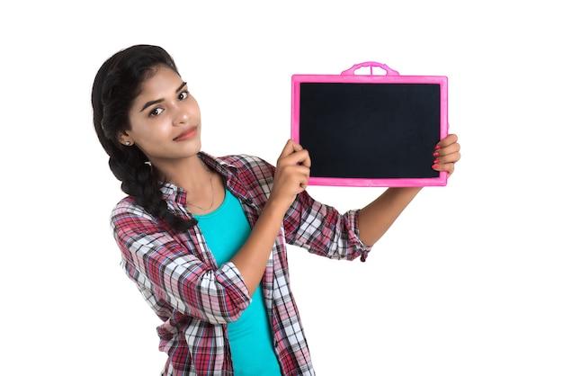 白い背景の上の黒板スレートを保持またはポーズをとって美しい少女