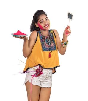 Красивая молодая девушка держит порошкообразный цвет в тарелке с карнавальной маской и небольшой вывеской по случаю фестиваля холи.