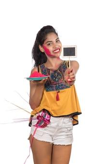 Holi 축제 행사에 카니발 마스크와 작은 간판과 함께 접시에 가루 색상을 들고 아름 다운 젊은 여자.