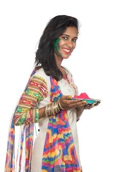 Holi 축제 행사에 접시에 가루 색상을 들고 아름 다운 젊은 여자.