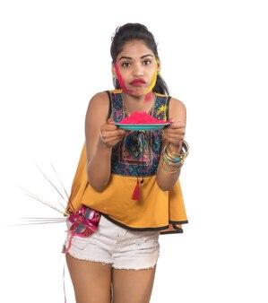 Красивая молодая девушка держит порошкообразный цвет в тарелке с карнавальной маской по случаю фестиваля холи.
