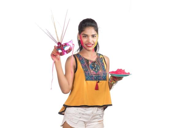 Holi 축제 행사에 카니발 마스크와 함께 접시에 가루 색상을 들고 아름 다운 젊은 여자.
