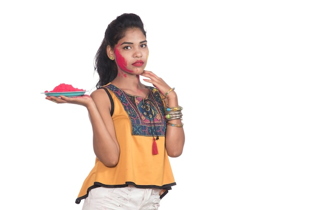 접시에 가루 색상을 들고 holi 축제를 계기로 색상을 즐기는 아름다운 어린 소녀.