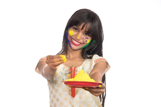 Beautiful young girl holding powdered color in plate on the occasion of holi festival