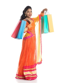 Beautiful young girl holding shopping bags while wearing traditional ethnic wear on white