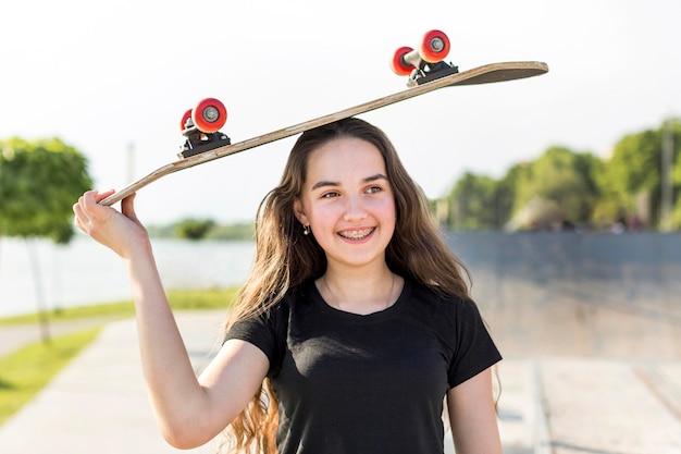 Bella ragazza che tiene uno skateboard sulla sua testa