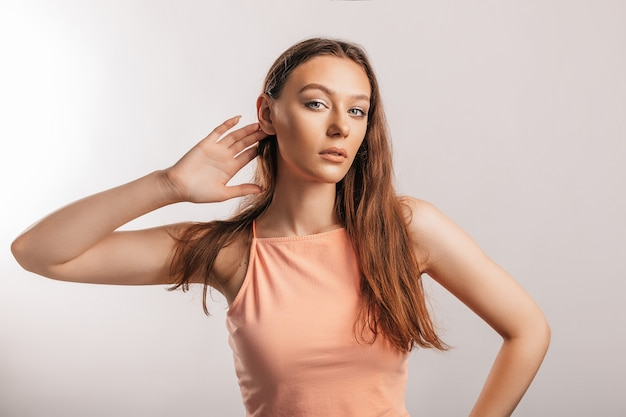 아름다운 어린 소녀는 귀 근처에 손을 잡고 광고 모형을 위한 장소가 있는 흰색 배경에서 더 잘 듣기를 원합니다
