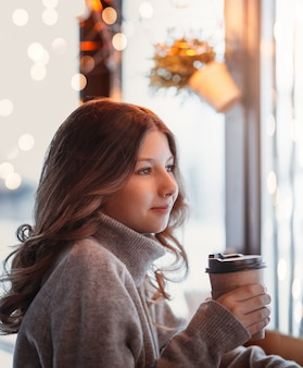 Beautiful young girl holds a paper cup of coffee and looks out the window of the cafe