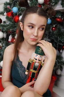Beautiful young girl holds a wooden nutcracker toy near a decorated christmas tree