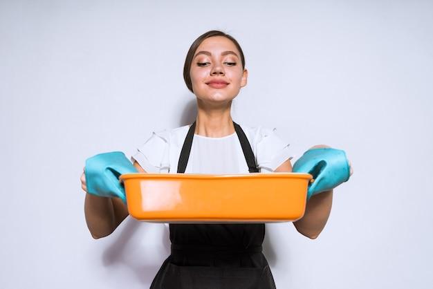 黒いエプロンで美しい若い女の子の主婦はオーブンでおいしいパイを作りました