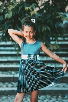 夏の公園でポーズをとって青いドレスを着た美しい少女。高品質の写真