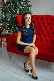 青いドレスの美しい少女は、クリスマスツリーの近くの赤いソファに座っています。クリスマスと新年の休日のコンセプトです。