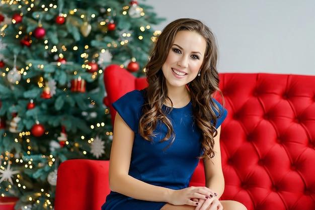 青いドレスの美しい少女は、クリスマスツリーと笑顔の近くの赤いソファに座っています。クリスマスと新年の休日のコンセプトです。