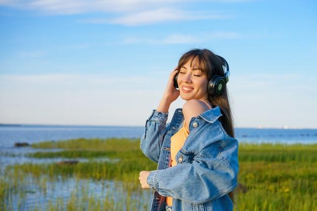 Красивая молодая девушка в джинсовой куртке слушает музыку в беспроводных наушниках