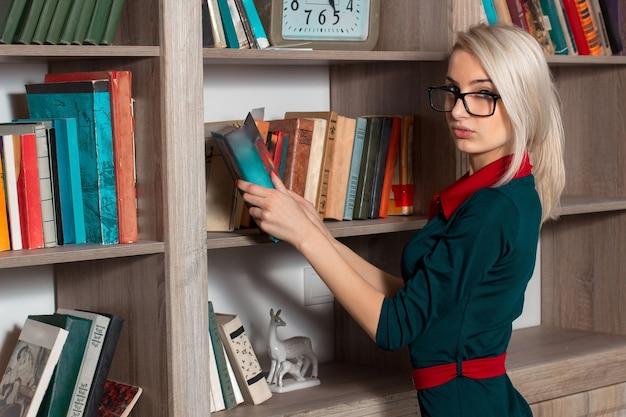 Красивая молодая девушка в платье кладет на книжную полку
