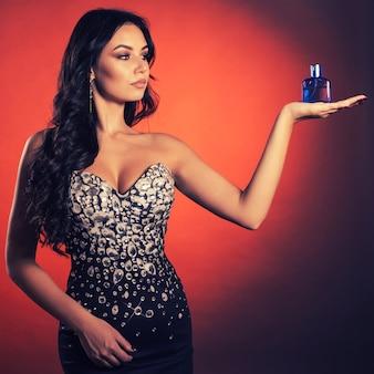 모조 다이아몬드와 드레스에서 아름 다운 젊은 여자는 빨간색 공간에 파란색 병에 향수의 손바닥에 보여줍니다