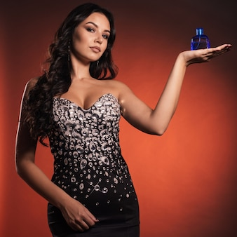 ラインストーンのドレスを着た美しい少女が香水の手のひらに表示されます