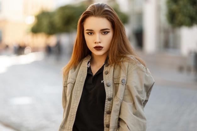 유행 재킷에 아름 다운 젊은 여자는 화창한 날에 도시에서 산책