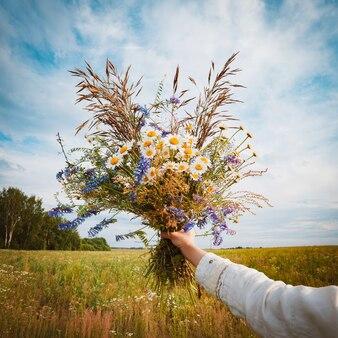 Красивая молодая девушка в поле цветов наслаждается ароматом и видом полевых ромашек