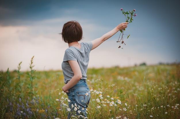 꽃의 분야에서 아름 다운 젊은여자가 필드 데이지의 향기와보기를 즐깁니다.