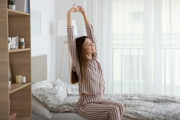 寝室のパジャマで良い気分の美しい少女