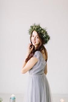 灰色のイブニングドレスと彼女の頭のポーズに松とユーカリの花輪の美しい少女