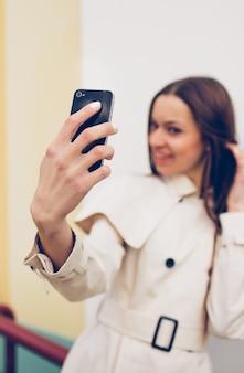 Красивая молодая девушка в легком плаще делает селфи на своем телефоне