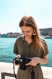 緑のカーキ色の明るい夏のドレスの美しい少女は、カメラを保持し、晴れた日に海岸でデジタル写真を見てください。旅行旅行のコンセプト。